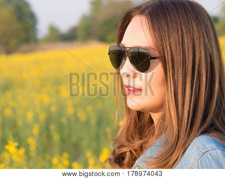 Asian Beautiful Woman In A Field Of Yellow Flowers, Put On Sunglasses And Jean Jacket. On A Sunny Da