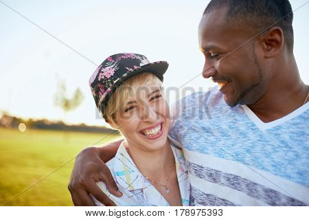 Diverse couple of tomboy girl and african american hipster guy in love hanging out in a city parc at sunset