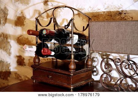 Decorative stand with wine bottles on table