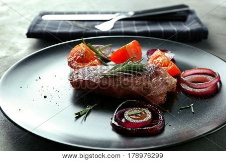 Delicious grilled steak with aromatic rosemary, tomatoes and onion on table
