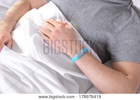 Young man with sleep tracker resting in bed at home, closeup