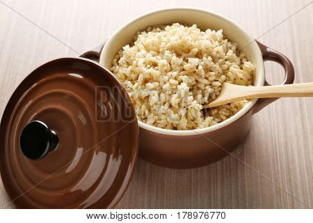 Modern ceramic saucepan full of boiled brown rice on wooden table