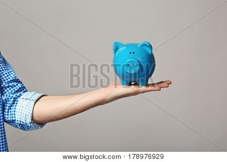 Male hand holding piggy bank on light background