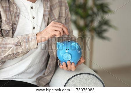Man putting coin into piggy bank, closeup