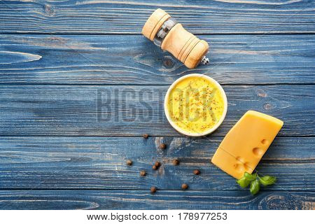 Bowl with cheese sauce and castor on wooden background
