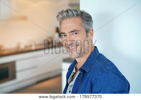 Smiling handsome 45-year-old man standing by home kitchen