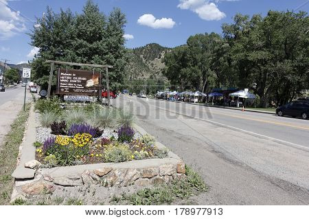 Idaho Springs CO USA - June 24 2016: A sign welcomes visitors to historic colorado mining country. Merchant Farmers market in park across the street