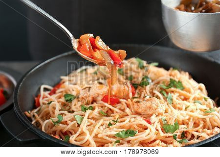Spoon with sauce over chicken spaghetti in frying pan