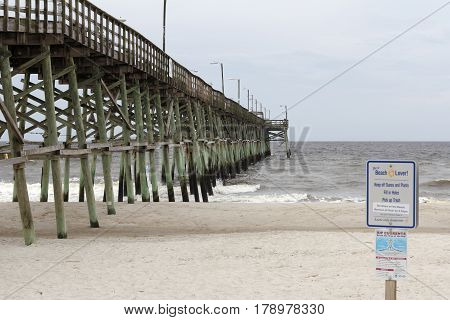 Oak Island NC USA - September 29 2016: Yaupon Fishing Pier over the Atlantic Ocean on an early day. Yaupon Fishing Pier on Oak Island beach in the morning.