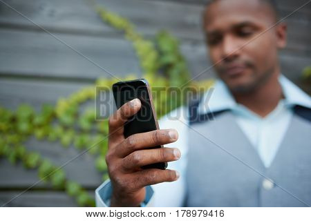 Attractive stylish African American millennial man checking and sending text messages on his smart phone by a wood gate in an ivy-filled urban setting