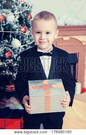 Beautiful little boy in a strict black suit , white shirt and tie.Boy near a Christmas tree with a gift in hand.Creative toning of a photograph.