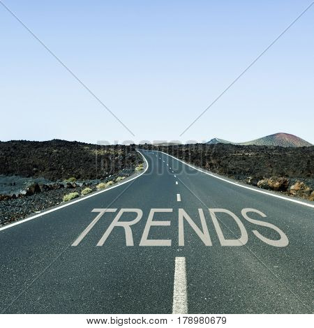 the word trends written in the asphalt of a lonely road with no traffic in a rural landscape