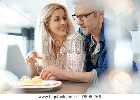 Cheerful middle-aged couple websurfing on laptop