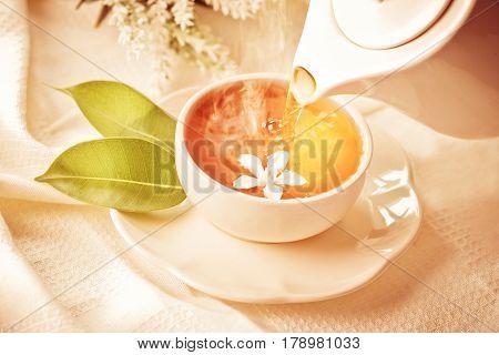 Close up pouring hot jasmine tea in a white tea cup Tea ceremony time concept vintage color tone