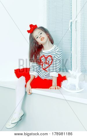Beautiful little girl a bright red bow on head and red skirt sitting by the window.She put one leg over the other.Creative toning of a photograph.