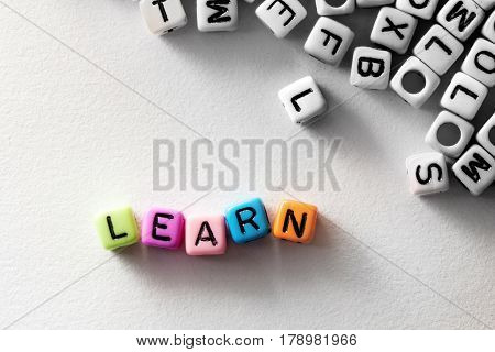 colorful LEARN word cube on white paper background English language learning concept