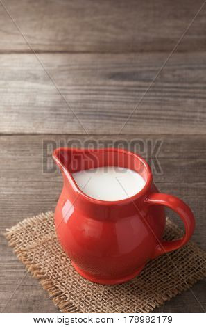 Milk in glass pitcher on white background wooden table