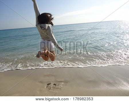 Photo jumping taken on sand and sea