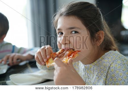 Portrait of kid eating slice of pizza