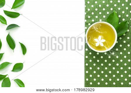 Top view shot of a hot cup of tea with green leaf decoration with green napkin on white background Organic green Tea ceremony time concept