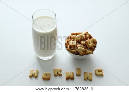 A Glass Of Milk, A Bowl Of Cookies With Inscription From The Cookies On The White Background.