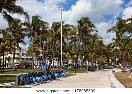 MIAMI BEACH FLORIDA - FEBRUARY 15 2017: Man uses a self service kiosk station to rent a bicycle on Ocean Drive in Miami Beach Florida USA on February 15 2017.