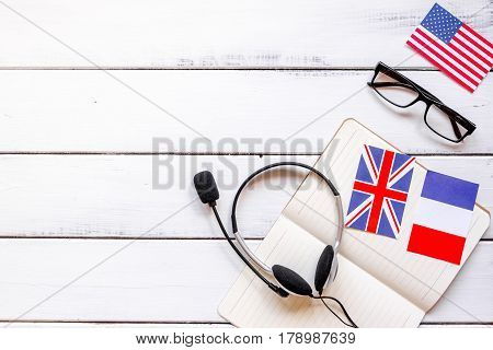 online education concept in learning language lifestyle with notebook and flags on white wooden desk background top view mockup