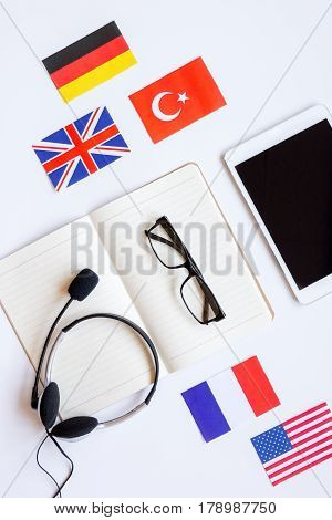 lifestyle learning english online with flags and tablet on white table background top view