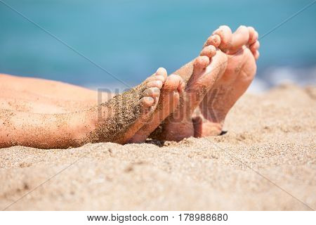 Mother with daughter relaxing and sunbathing on a beach