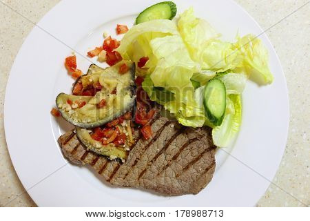 Grilled minute steak slice, seen from above, garnished with eggplant (aubergine) and chopped tomatoes topped with grated cheese and served with a lettuce and cucumber salad
