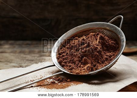 Metal sieve with cocoa powder on kitchen table