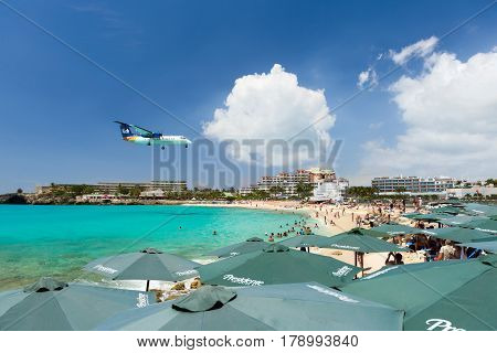 ST MAARTEN CARIBBEAN - SEPTEMBER 21 2013: airplane landing over the sea beach of Maho bay Caribbean