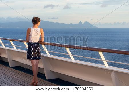 young woman in dress stands on the deck of cruise liner and looking at the ocean