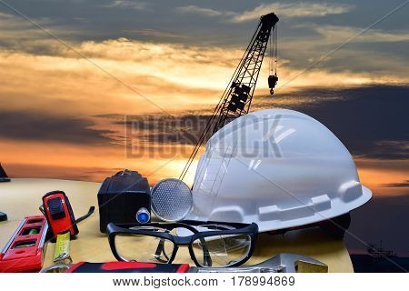 Double exposure of  safety helmet and safety equipment  on  construction background ,Work safety at construction site concept .