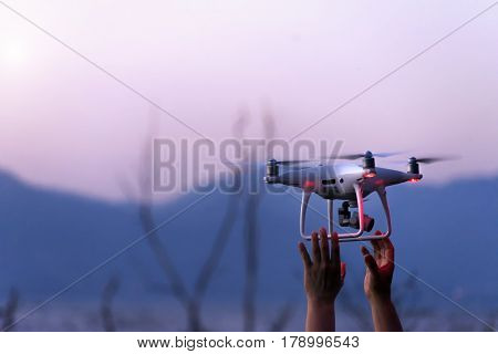 The drone and photographer man hands , The drone with the professional camera takes pictures.