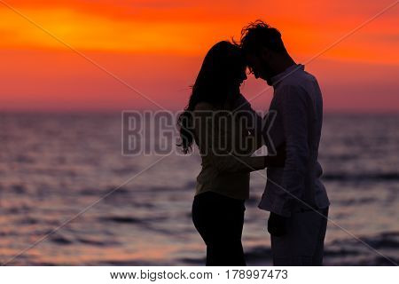 sunset silhouette of young couple in love hugging at beach.