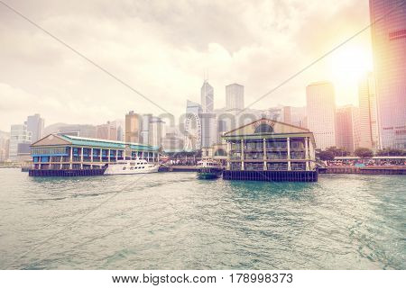 Late afternoon sunset over Central Ferry Pier on Hong Kong Island with the downtown business district in the background. With its Edwardian architecture the pier also known as Star Ferry Pier was built in 2006.