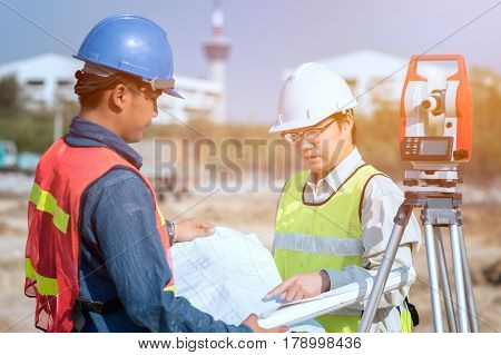 Construction engineer and foreman worker checking construction drawing at site for new Infrastructure construction project