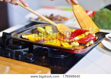 Vegetable ragout in pan, on wooden table on bright background.