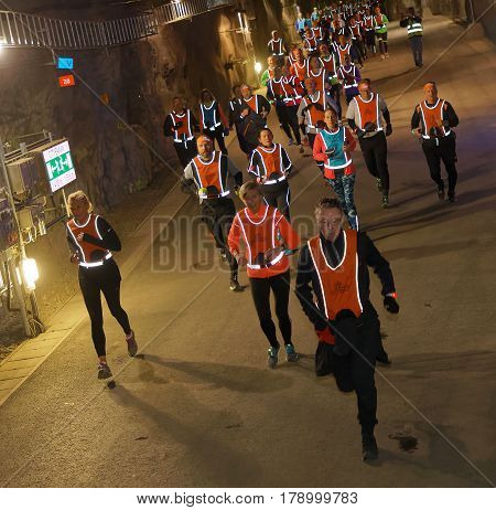 STOCKHOLM SWEDEN - MAR 25 2017: Large group of runners from above in a dark tunnel in the Stockholm Tunnel Run Citybanan 2017. March 25 2017 in Stockholm Sweden