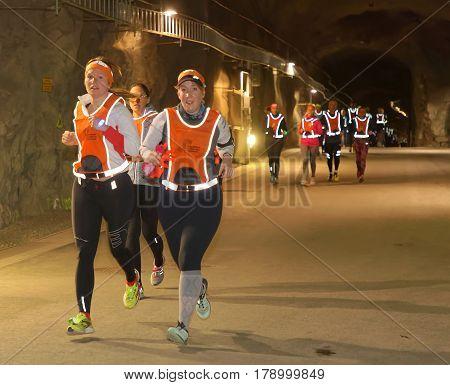 STOCKHOLM SWEDEN - MAR 25 2017: Girls in reflex vest running in a dark tunnel in the Stockholm Tunnel Run Citybanan 2017. March 25 2017 in Stockholm Sweden