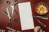 Blank card with barber tools flat lay. Top view on red table with scissors, razor, hair wax and shaving brush with empty white paper, free space. Barbershop, manhood concept poster