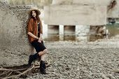 stylish boho woman with jewelry posing at rock wall. beautiful gypsy dressed girl with hat and fringe poncho with sensual look. young girl traveler. fashionable hippie outfit. space for text poster