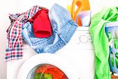 Messy laundry clothes on washing machine room at home - Colorful clothing on top and inside washer with detergent powder and bottles - Concept of housework and energy expense - poster