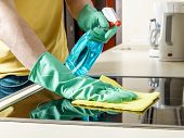 Caucasian man cleaning the cooker in the kitchen with yellow rag spray and gloves poster