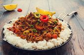 Slow Cooker Ropa Vieja Cuban famously delicious shredded beef stew with pepper and olives on a black plate with a boiled rice and fresh lemon on the wooden table. poster