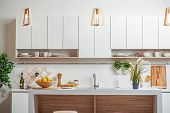 Cozy kitchen with furniture in contemporary style. Wooden chandeliers are hanging under white counter near sink and cupboards. Healthy fruits on board poster