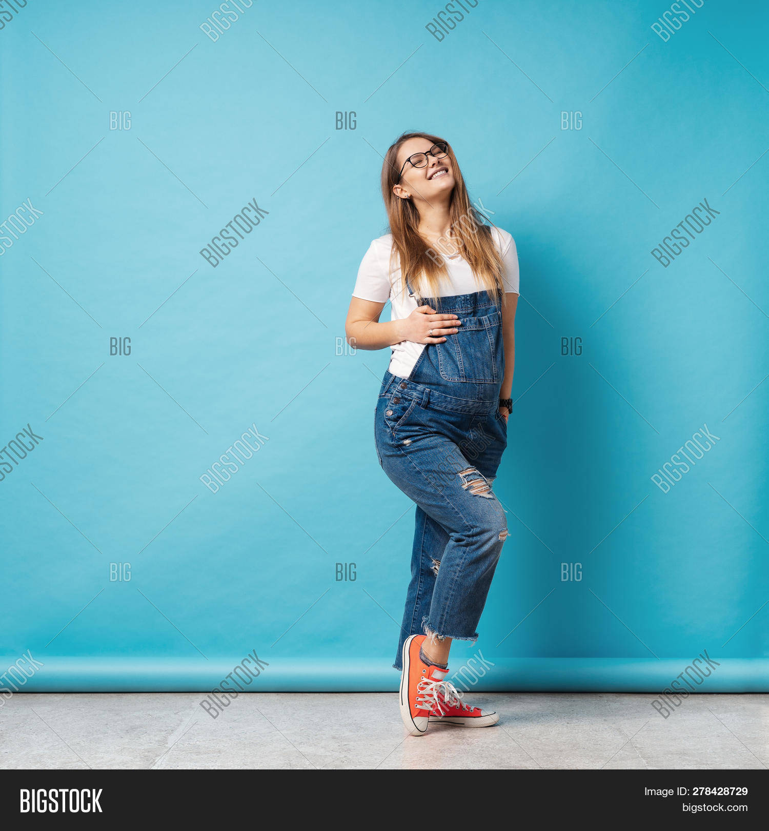 792247318f9 Pregnant Woman Caressing Her Belly Over Blue Background. A Cute Young Woman  Wearing Glasses