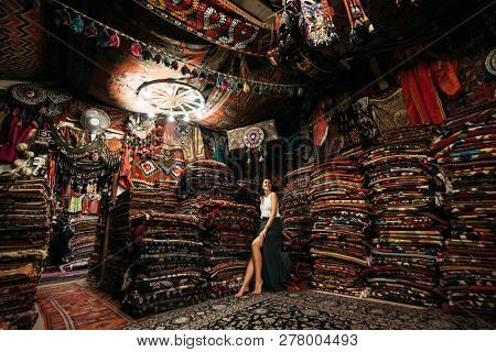 Girl In A Carpet Store. Happy Woman Customer Choosing Colored Carpet In Carpet Store. Girl In Turkis