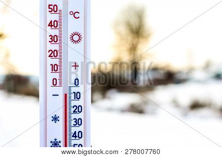 The Thermometer On The Blurred Background Of The Winter Landscape Shows A Subzero Temperature